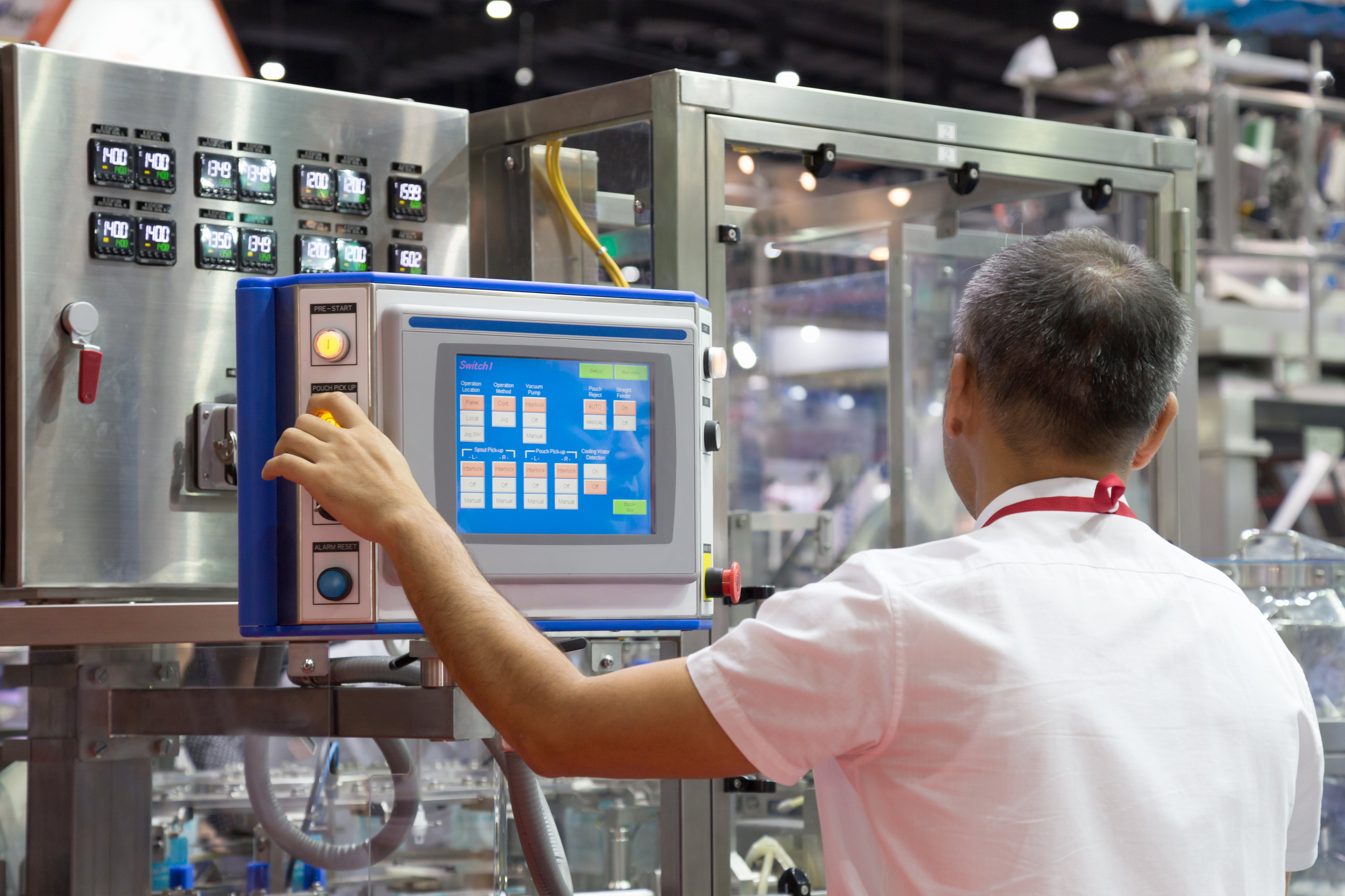 Man using a control panel in an automated factory