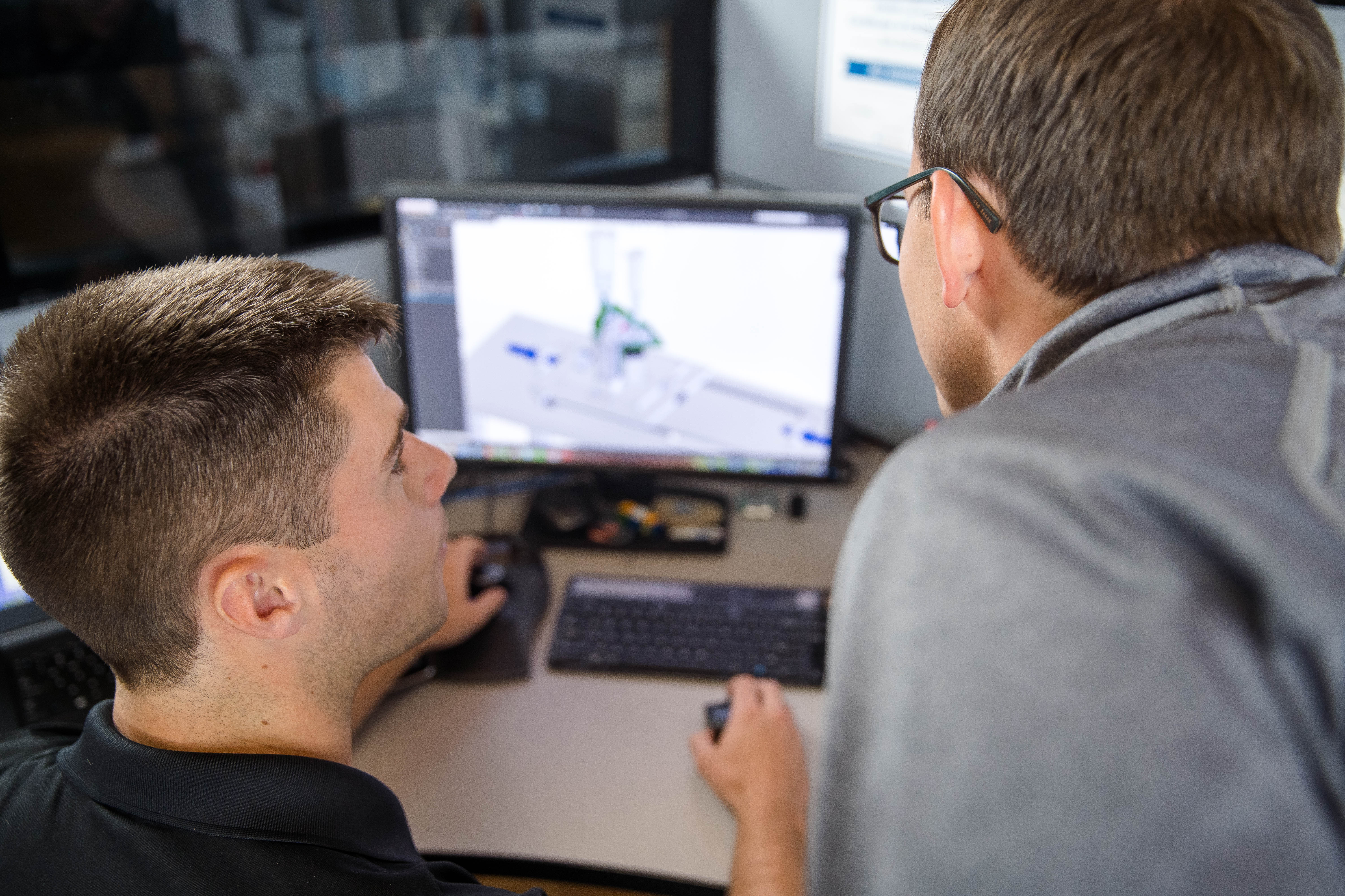 Two engineers looking at a CAD model on computer